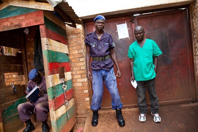 Prisoner and guard outside the main entrance of the Ruyigi district prison, Burundi.