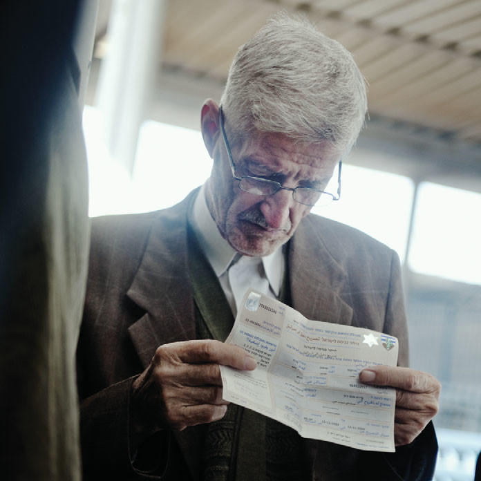A Palestinian fidgets with his permit while waiting in line at an Israeli checkpoint at Kalandia, 2009.