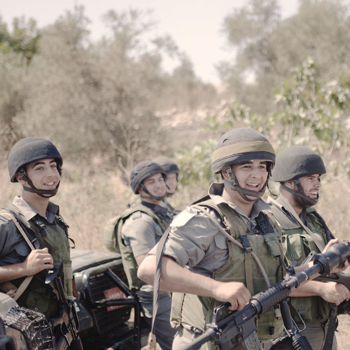 Israeli soldiers smile after firing tear gas at demonstrators in the West Bank, 2010.