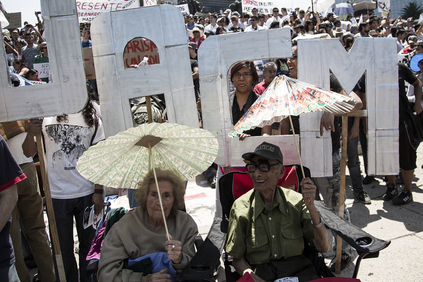 Elderly activists hangout in the hot mid-day sun during  the #YoSoy132 march. Older marchers like this remember demonstrating against the PRI in past  decades. They often paid for it in blood.