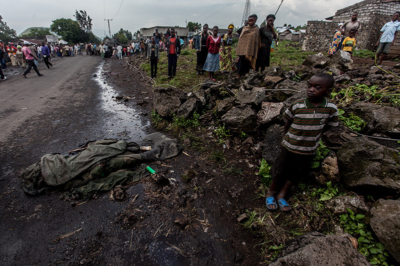 A young boy stands by the corpse of a slain FARDC soldier in Goma on 21 November, 2012.