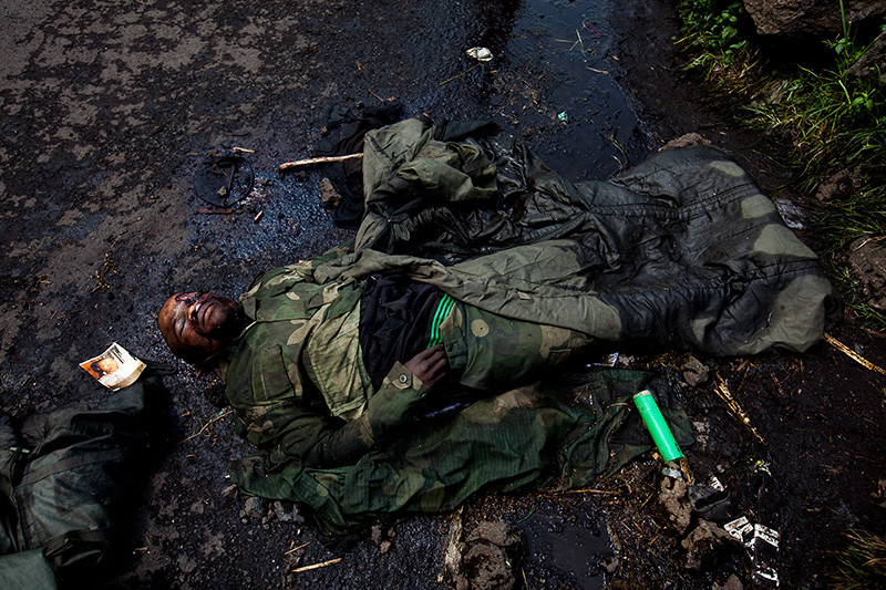 The corpse of a slain FARDC soldier lies at the side of the road.