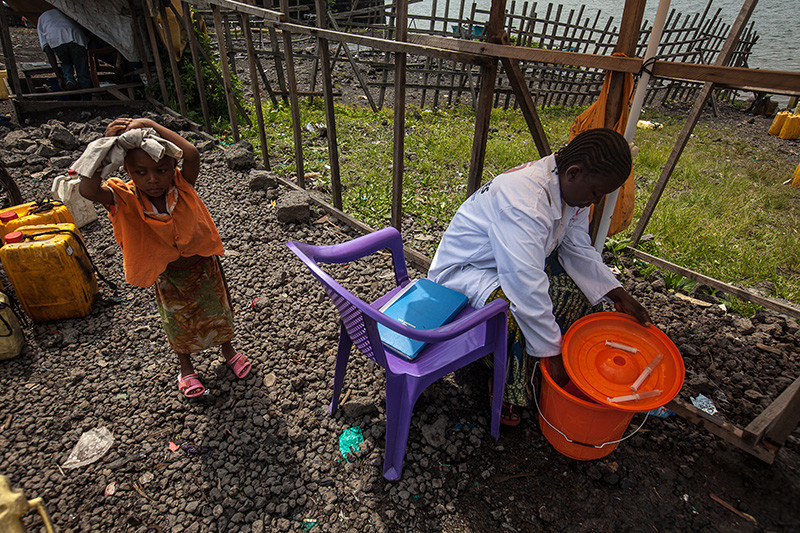 A woman fills a syringe of chlorine, used to sterilise water drawn from Lake Kivu in Goma on November 22, 2012. Water supplies were cut as rebels entered Goma on November 20, 2012.