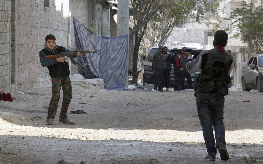 November 21, 2012 – Aleppo, Syria: Young Free Syrian Army fighters playing near a sniper alley located in the neighborhood of Amreyah.