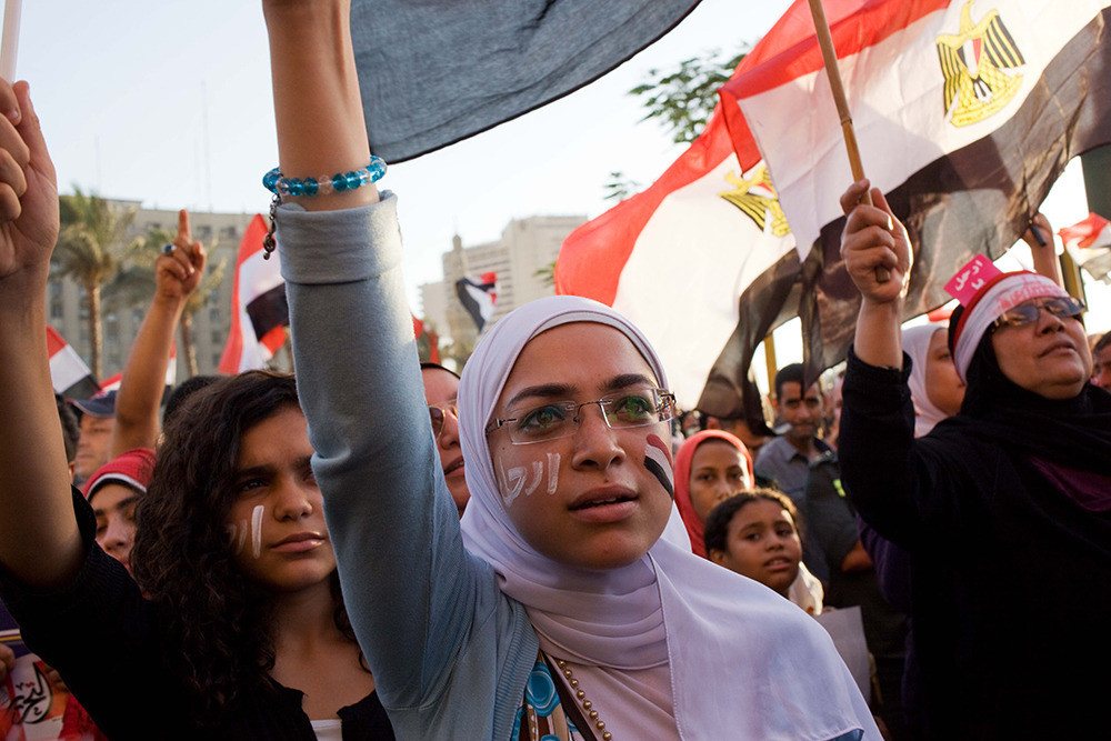 "A young Egyptian woman protests with others in Tahrir Square on June 28. Crowds chanted, ""Erhal! Erhal! Erhal!""—""Leave! Leave! Leave!"""