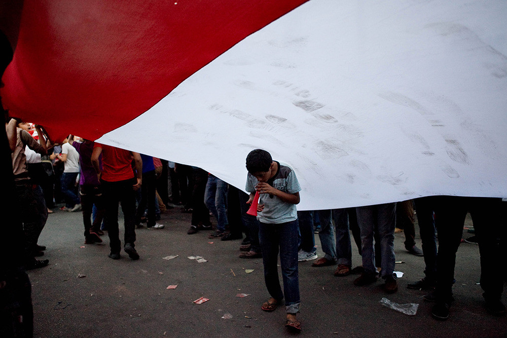 July 1: A young Egyptian boy plays a plastic horn underneath a giant Egyptian flag.