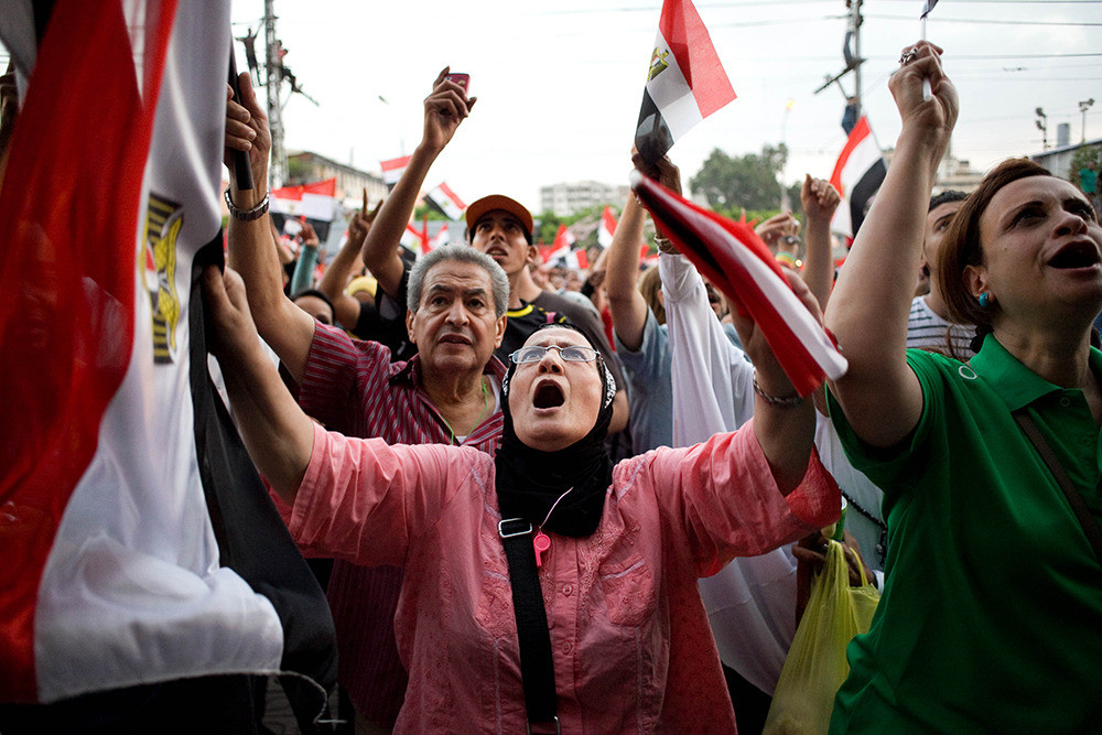 July 1: An Egyptian woman sings and chants slogans against President Morsi outside the presidential palace.