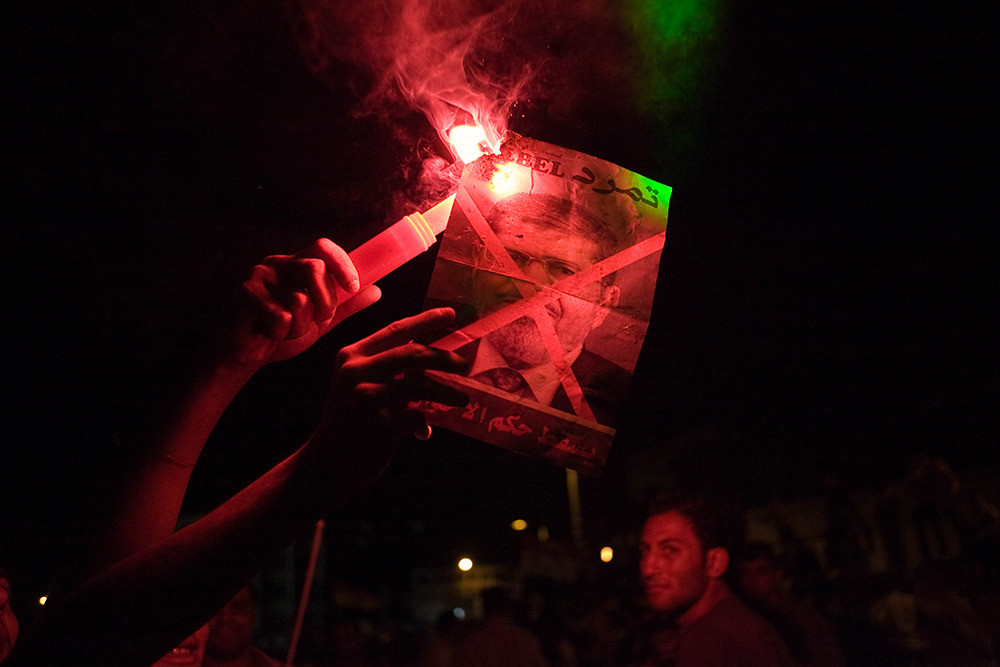 July 1: Protesters set fire to a poster of President Morsi with a flare.
