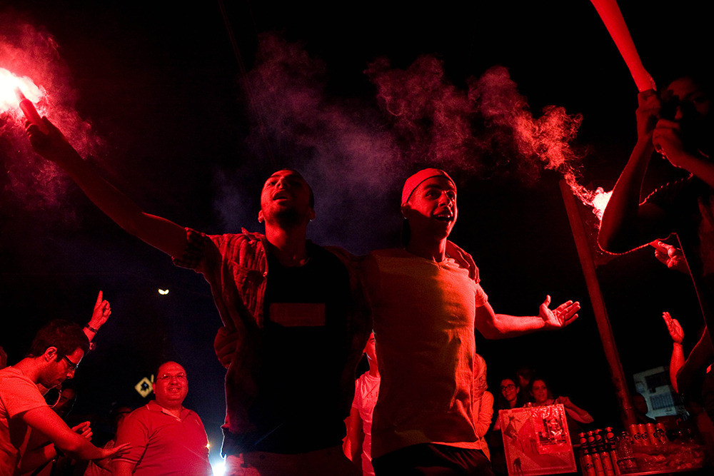 July 1: Protesters light flares and dance outside the presidential palace, demanding President Morsi resign.