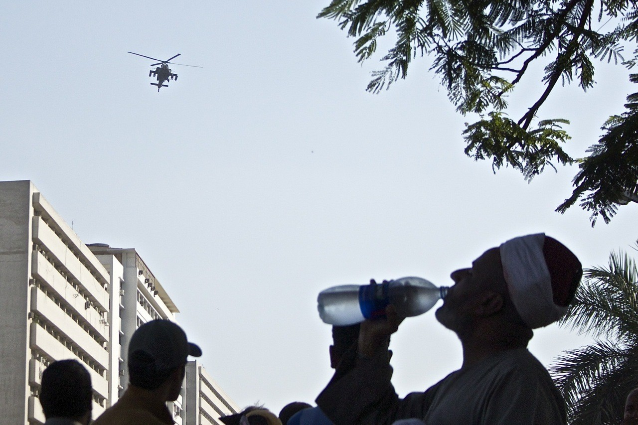 A military helicopter flies over a demonstration in support of Morsi.