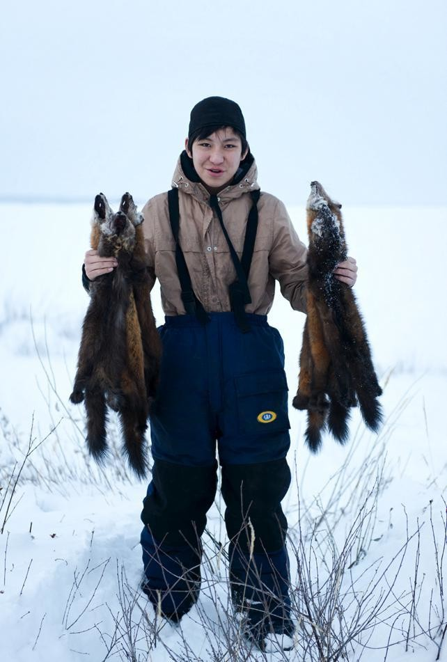 Adrian Oudzi holds up the marten he trapped.